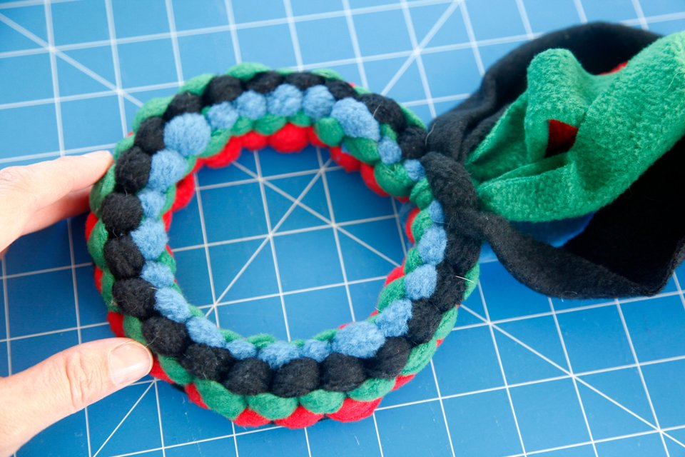 Weaving a DIY fleece loop dog tug toy to create a round circle