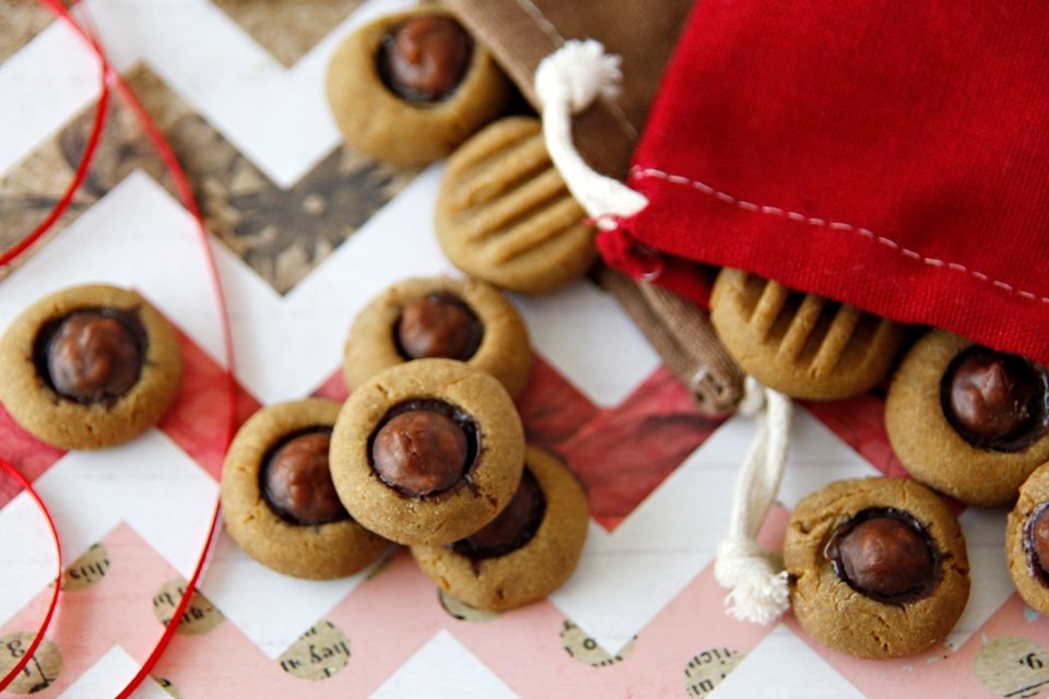 Homemade peanut butter molasses dog treats topped with carob drop kisses.