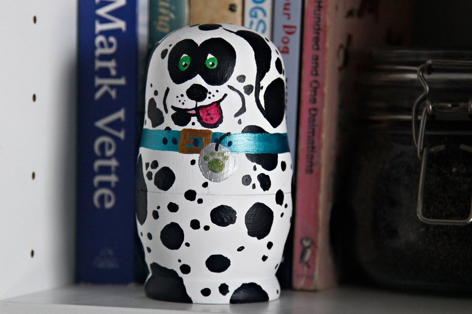 Painted Dalmatian dog nesting doll sitting on a bookshelf